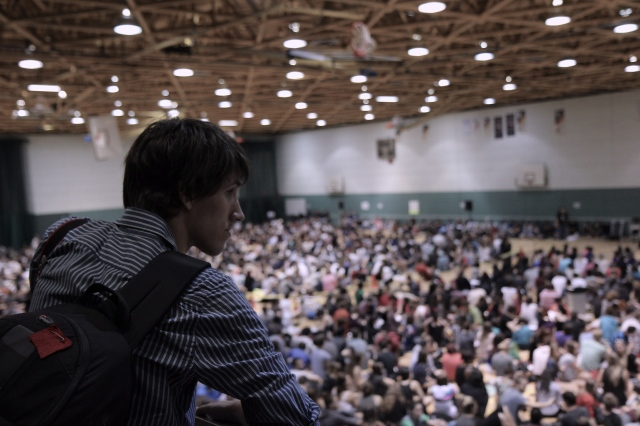 """A student with the """"carré rouge"""" pinned to his backpack looks out over the General Assembly at CÉGEP du Vieux-Montréal"""